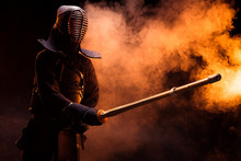 Kendo Fighter In Armor Practicing With Bamboo Sword In Smoke