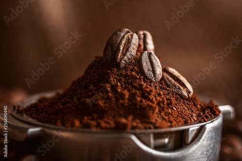 Photo sur Aluminium Café en grains ground coffee poured into the holder on which the grains of roasted, fragrant coffee lie. on the background of fried grains