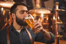 Bearded Male Brewer Sipping Delicious Ber From A Glass, Working At His Production Brewery. Professional Brewer Tasting Fresh Beer At His Microbrewery, Drinking With His Eyes Closed. Pleasure Concept