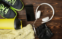 Flat Lay Of Mobile Phone With Earphone And Sport Equipment On Wood Background