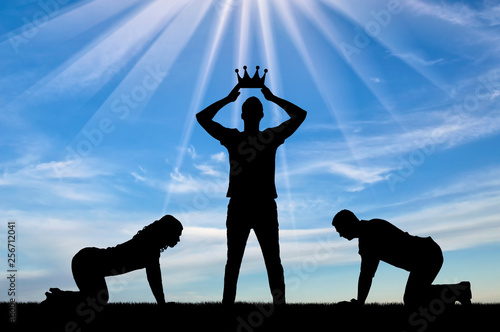 Photo Silhouette of a man and a woman worshiping a man who puts a crown on his head