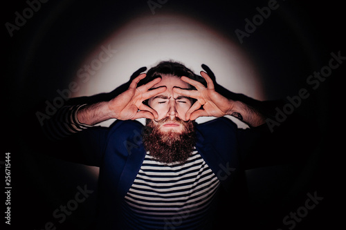 Fotografie, Obraz  bearded man in a circle of light with different emotions