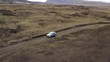 Aerial drone shot following a SUV driving on a gravel road into Highlands of Iceland