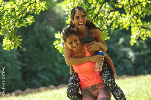 Two best female friends making fun after jogging and workout.They laughing and carrying each other.Spring time. - 256731062