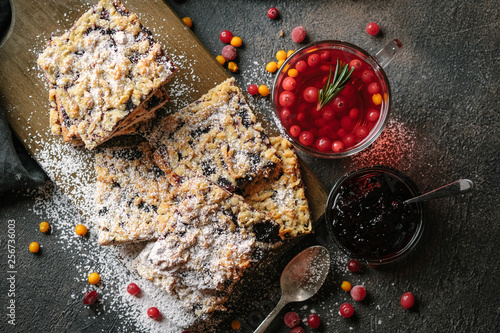 Delicious homemade cake with berry jam for tea on a dark background.