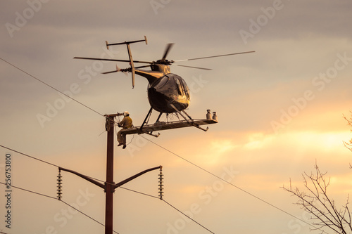 Poster Helicopter Helicopter hovering in flight with man sitting on the outside fixing power lines repairing wires