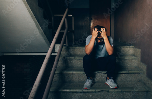 Photo  Depressed man sitting on the stairs in building and holding his forehead while having headache