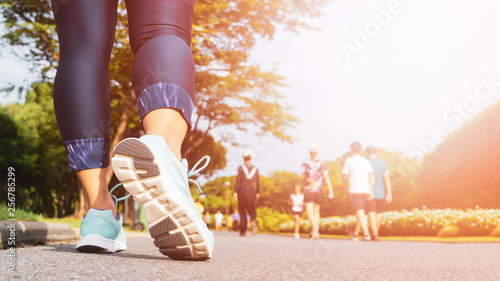 Fotografie, Obraz  Young fitness woman legs walking with group of people exercise walking in the city public park in morning