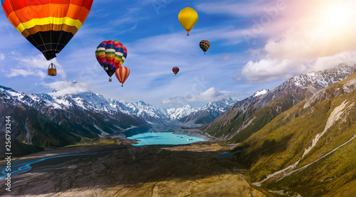 Tuinposter Ballon Beautiful panoramic nature landscape of countryside mountains with colorful high hot air balloons festival in summer sky. Vacation travel panorama background.