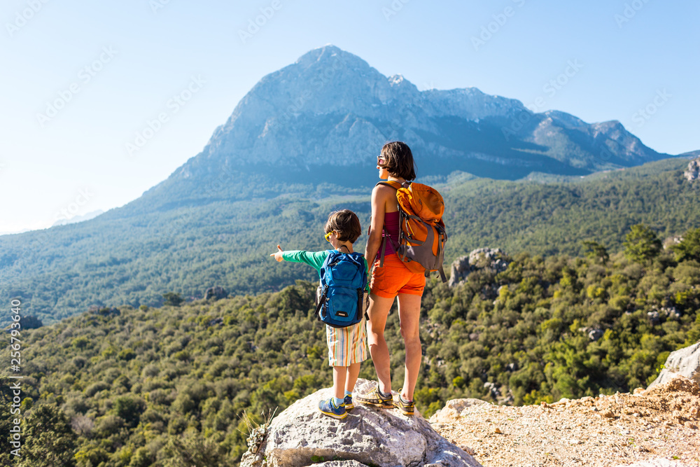 Fototapety, obrazy: The boy and his mother are standing on the top of the mountain.