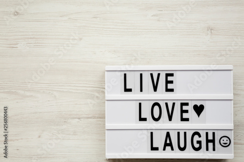 """Live Love Laugh' words on lightbox over white wooden surface, top view Wallpaper Mural"