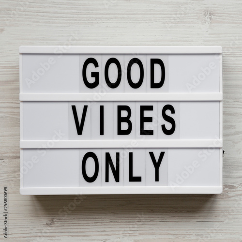 Fotografía  'Good vibes only' words on lightbox over white wooden surface, top view