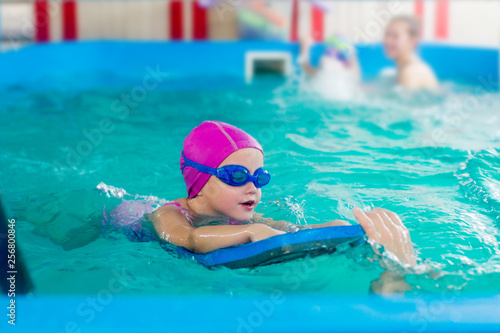 Fototapety, obrazy: A female child in a pink rubber hat and blue glasses is swimming in a pool with a swimming board.