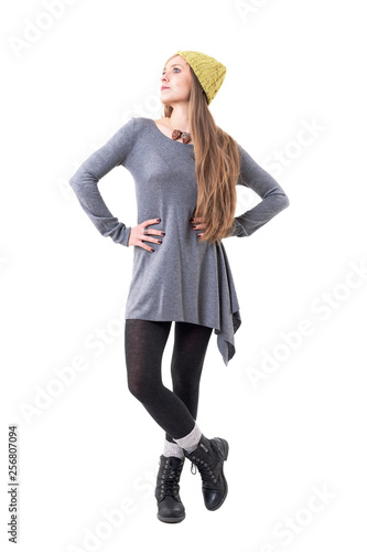 Fotografie, Obraz  Young blonde woman in authentic fashion wearing yellow beanie cap and gray tunic looking up