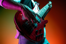 African American Handsome Jazz Musician Playing Bass Guitar In The Studio On A Neon Background. Music Concept. Young Joyful Attractive Guy Improvising. Close-up Retro Portrait.