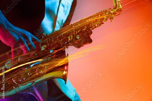Fényképezés African American handsome jazz musician playing the saxophone in the studio on a neon background
