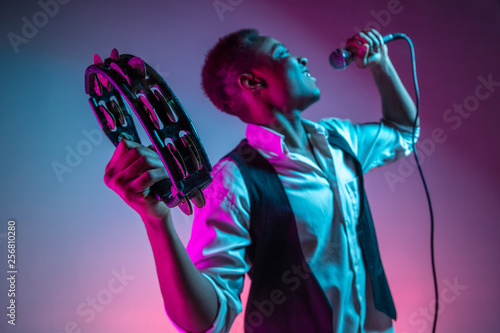 African American handsome jazz musician playing tambourine and singing into the microphone in the studio on a neon background Fototapeta