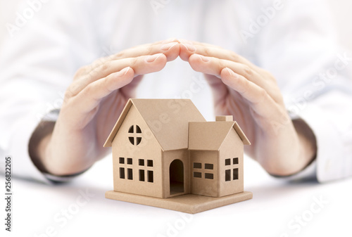 Property insurance. House miniature covered by hands. Wallpaper Mural