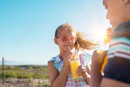 Foto auf Gartenposter Saft Children drinking orange juice outdoor
