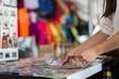 Leinwanddruck Bild - A tourist buying handmade crafts at a giftshop.