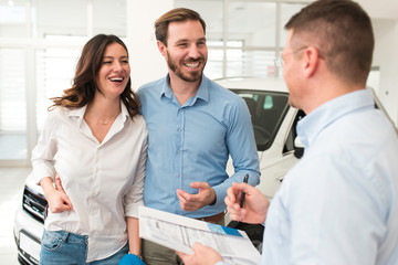 Young happy excited beautiful couple smiling while buying a new car. Signing a contract with seller in car salon.