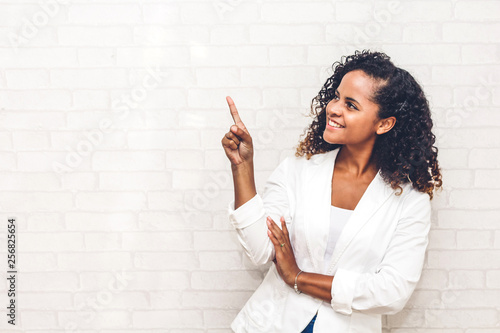 Fototapeta Smiling african american black woman pointing to empty copy space standing on white brick wall background obraz