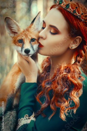 Beautiful lady is posing with a red fox in the forest Canvas Print