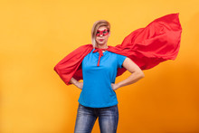 Young Woman In Superheros Costume Standing Proudly With Her Red Cape In The Air Over Yellow Background