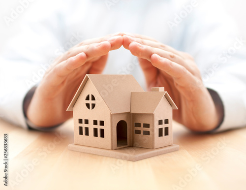 Photo  Property insurance. House miniature covered by hands.