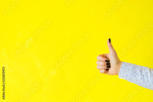 Valokuva  Person showing thumbs up hand gesture on empty yellow background