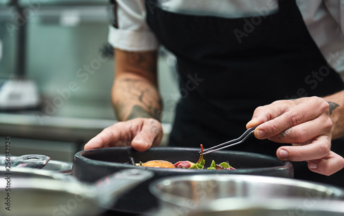Fototapeta Creative Cooking. Cropped image of chef hands garnishing Pasta carbonara in a restaurant kitchen. obraz