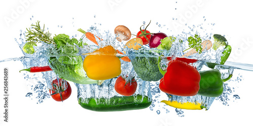Poster Cuisine fresh vegetables splashing into blue clear water splash healthy food diet freshness concept isolated white background