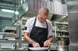Finishing a dish. Attractive male chef with beautiful tattoos on his arms garnishing his dish on the plate in restaurant kitchen