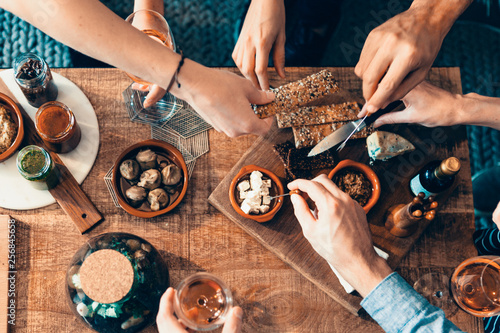 Leinwand Poster high angle view of hands picking up food from a table: togetherness, friendship,