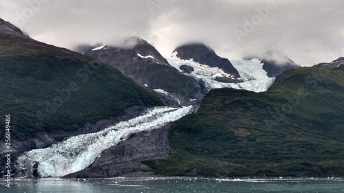Glaciers within Glacier Bay National Park in Alaska. Glaciers coming over mountain peaks and sliding into the Pacific Ocean