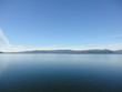 Passage in the Pacific Ocean between two mountain ranges. Calm peaceful waters flowing slowly under a cloudy sky.