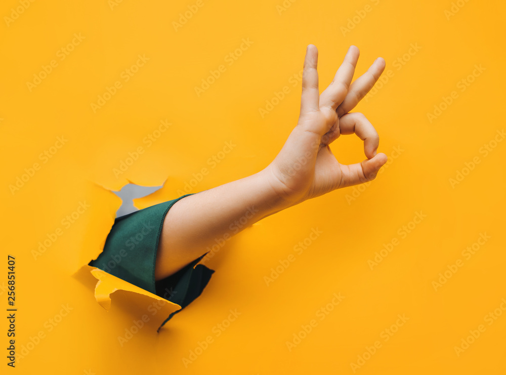 Fototapety, obrazy: Hand OK sign. The teenage hand came out into the hole of yellow paper and shows symbol of Okay. Copy space, fine.