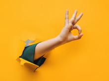 Hand OK Sign. The Teenage Hand Came Out Into The Hole Of Yellow Paper And Shows Symbol Of Okay. Copy Space, Fine.