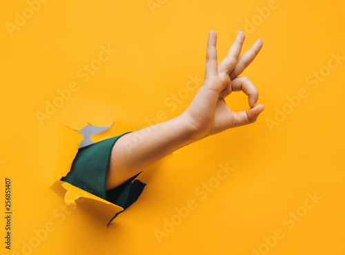 Obraz Hand OK sign. The teenage hand came out into the hole of yellow paper and shows symbol of Okay. Copy space, fine. - fototapety do salonu