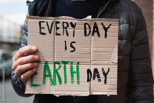 Photo  text every day is Earth day in a brown signboard