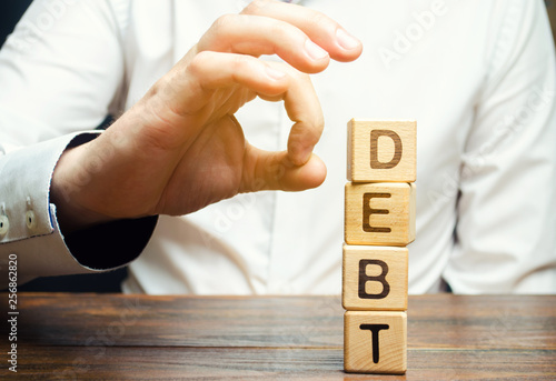 Obraz na płótnie Businessman removes wooden blocks with the word Debt