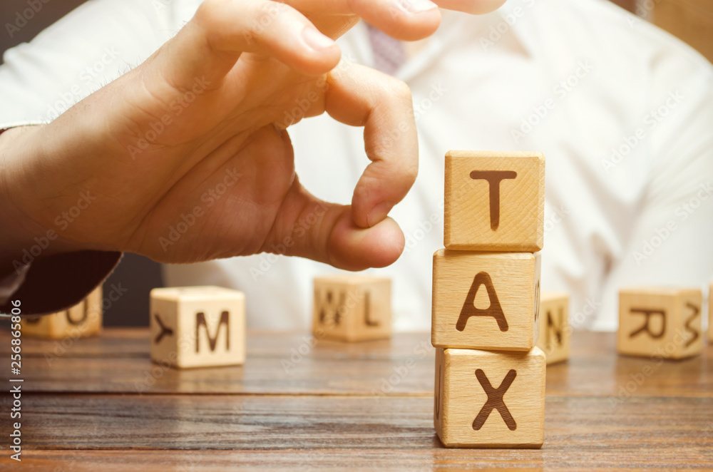 Fototapeta Businessman removes wooden blocks with the word Tax. The concept of reducing the tax burden. Tax avoidance. Costs and expenses of the business. Taxation. Pay off debt. Freedom from illegal taxes