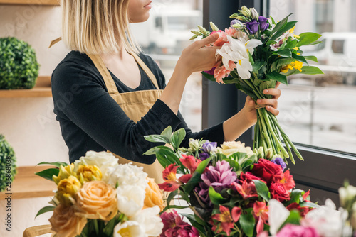 Fotografía  Cropped view of florist in apron holding bouquet in flower shop
