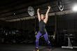Fit young woman lifting barbells looking focused, working out in a dark gym - Image