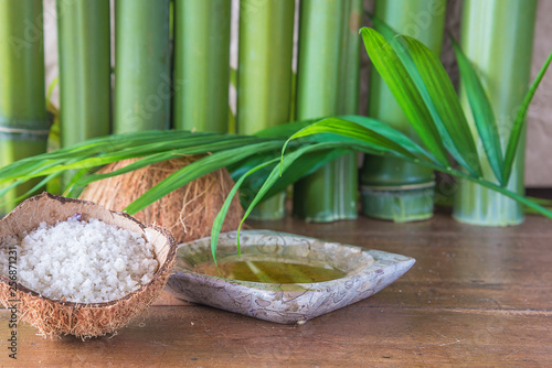 Foto op Plexiglas Stenen in het Zand Spa or body care concept: sea salt in the coconut, massaging oil, palm leaf and bamboo trunk on old wooden background