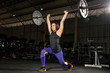 Muscular woman in gym doing heavy weight exercises. Young woman doing weight lifting at health club in a dark gym. - Image