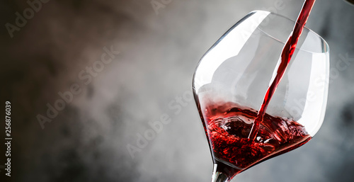 Photo sur Toile Vin French dry red wine, pours into glass, gray background, banner, selective focus
