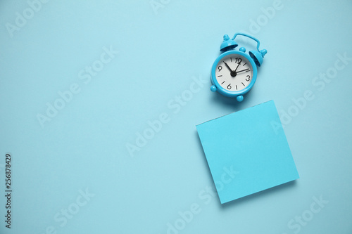 Obraz Blue alarm clock and a reminder note. Time management concept. Copy space for text. - fototapety do salonu