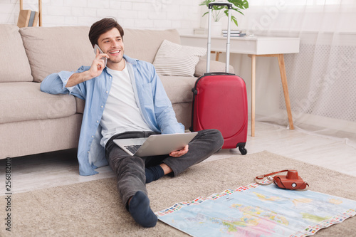 Young man preparing for vacation, consulting with agent