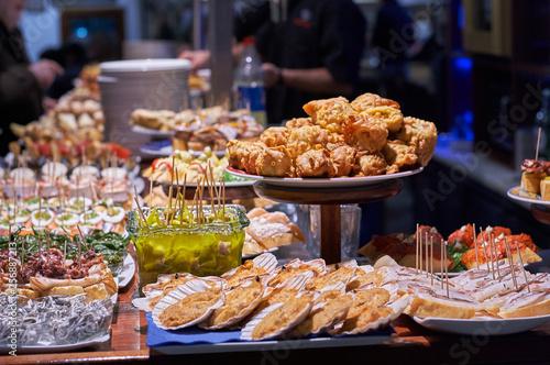 Fototapeta premium Pinchos i tapas typowe dla Kraju Basków w Hiszpanii. Wybór różnych rodzajów żywności do wyboru. San Sebastian